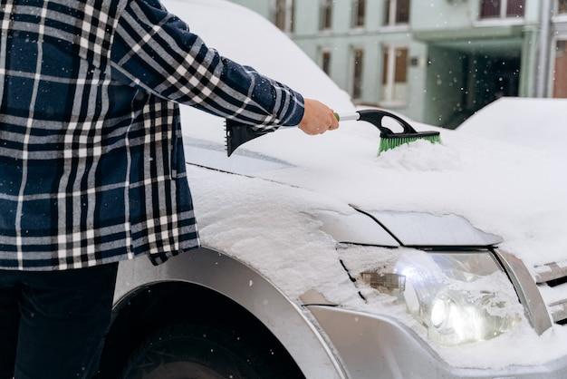 Bijgesneden weergave van de blanke man die sneeuw van zijn auto schoonmaakt tijdens de wintersneeuw. transport- en seizoenenconcept