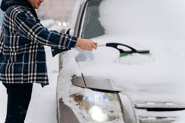 Bijgesneden weergave van de blanke man die sneeuw van zijn auto schoonmaakt tijdens de wintersneeuw. transport-, voertuig- en autoverzorgingsconcept in de winter