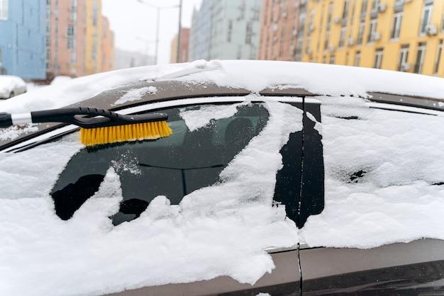 Bijgesneden weergave van de geparkeerde auto bedekt met sneeuw na sneeuwval in de winter. onherkenbare persoon die een speciale borstel gebruikt om de auto van de sneeuw te reinigen