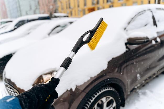 Bijgesneden weergave van de onherkenbare persoon die een speciale borstel gebruikt om de auto van de sneeuw te reinigen. geparkeerde auto bedekt met sneeuw na sneeuwval in de winter