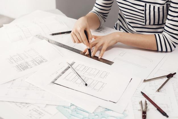 Bijgesneden weergave van jonge knappe vrouwelijke ontwerper die strepenoutfit draagt, op comfortabele lichte werkplaats zit, die aan nieuw ontwerpproject werkt met pen, heerser en document.