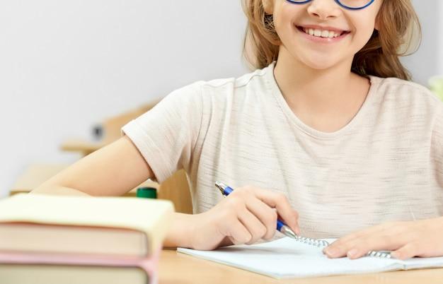 Bijgesneden weergave van lachende student zitten aan de balie op school