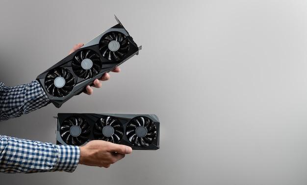 Bijgesneden weergave van man met twee videokaarten op grijze achtergrond. bitcoin cloud mining