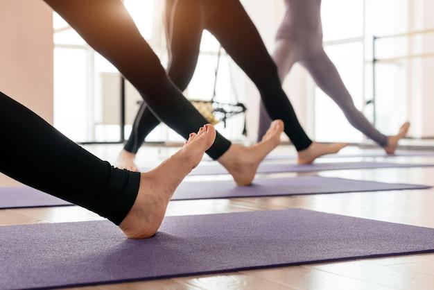 Bijgesneden weergave van meisjes die yoga uitoefenen, voeten en benen strekken die zich in een rij bevinden