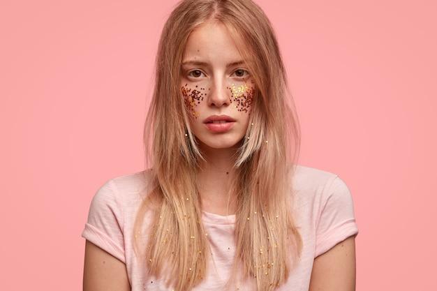 Bijgesneden weergave van mooie vrouw heeft wangen versierd met glitters, ziet er zelfverzekerd uit
