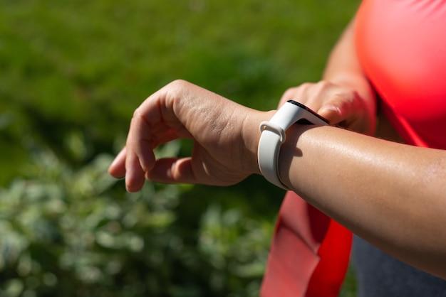 Bijgesneden weergave van sportvrouw kijken naar fitness tracker met hartslag tarief. concept van het gebruik van moderne technologie en gadgets in de sport
