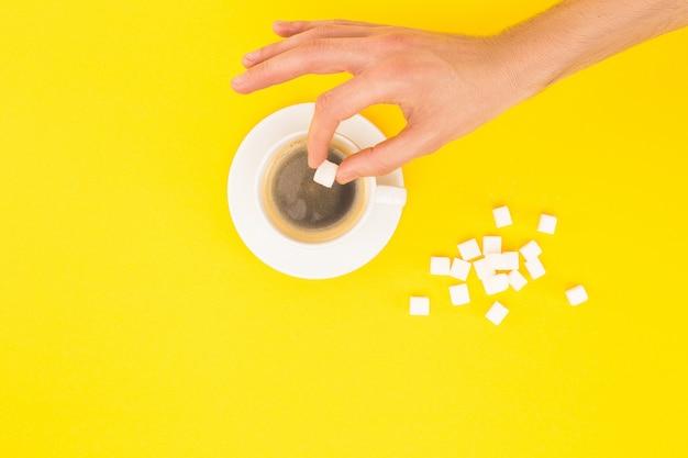 Bijgesneden weergave van vrouw klontjes suiker toevoegen aan koffie geïsoleerd op geel