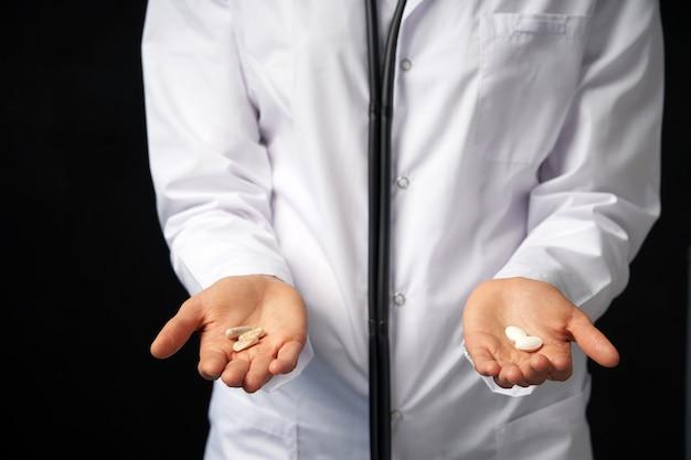 Bijgesneden weergave van vrouwelijke arts bedrijf in handen pillen om uit te kiezen. moeilijke keuze tussen medicijnen. placebo drugs concept. gezondheidszorg concept.