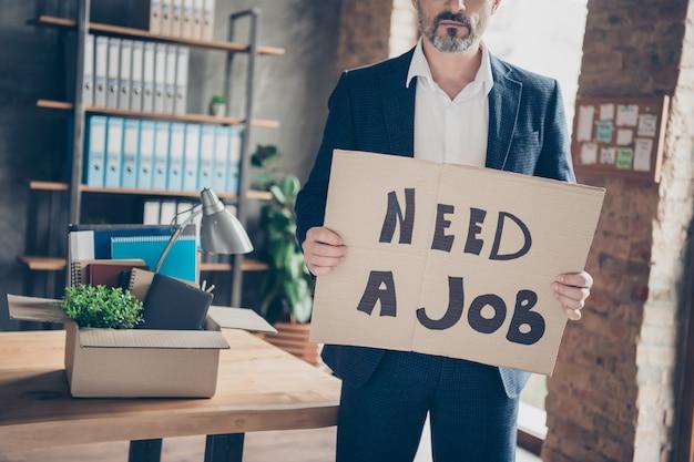 Bijgesneden weergaveportret van zijn serieuze werkloze kerel econoom werkgever die in handen plakkaat houdt met de mededeling dat hij een baan nodig heeft menselijke bezetting bij moderne loft industriële bakstenen stijl interieur werkplek werkstation