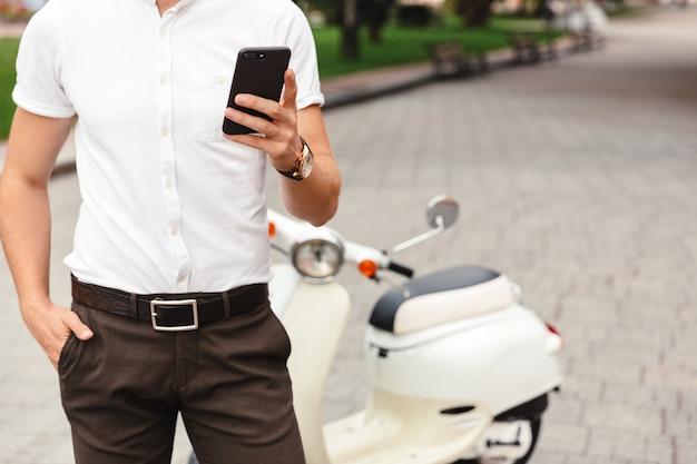 Bijgesneden zakenman met behulp van smartphone terwijl hij buiten in de buurt van de scooter
