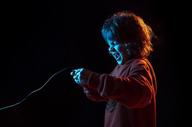 Bijgewoond spelen van videogames. het portret van de kaukasische jongen op donkere studioachtergrond in neonlicht. prachtig krullend model. concept van menselijke emoties, gezichtsuitdrukking, verkoop, advertentie, moderne technologie, gadgets.