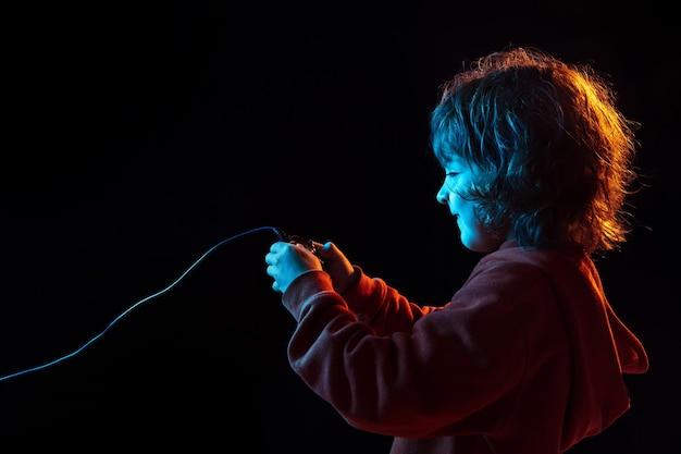 Bijgewoond spelen van videogames. het portret van de kaukasische jongen op donkere studioachtergrond in neonlicht. prachtig krullend model.