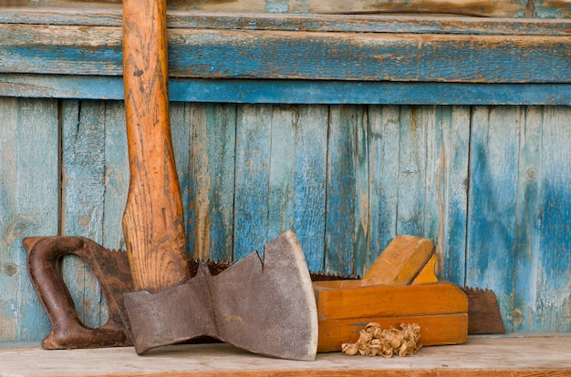 Bijl, schaafmachine en zaag op een oude houten tafel, chips