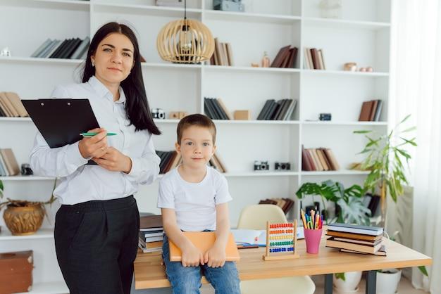 Bijlesdocent behandelt de kleuter met een laptop, een echt interieur, het concept van kindertijd en leren
