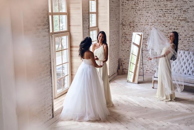 Bijna gereed. bovenaanzicht over de volledige lengte van bruidsmeisjes die de bruid helpen aan te kleden terwijl ze samen bij het raam staan