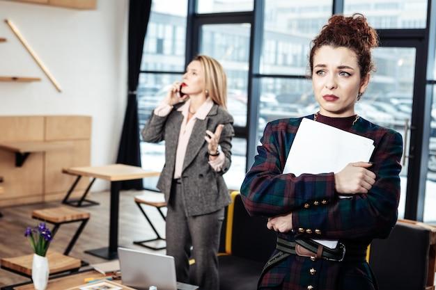 Bijna huilen. jonge onervaren aantrekkelijke secretaresse die de strikte vrouwelijke baas bijna huilend achterlaat