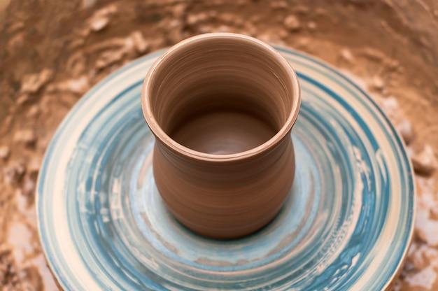 Bijna voltooid aardewerk van klei op een draaiend pottenbakkerswiel