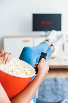 Bijs vrouw met popcorn het letten op op reeks in woonkamer
