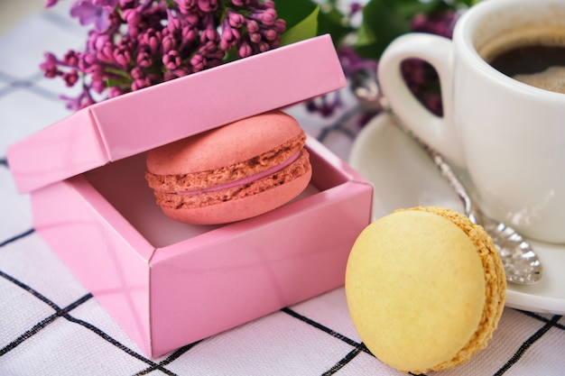 Bijsnijden kopje koffie en lekkere zoete macarons in geschenkverpakking