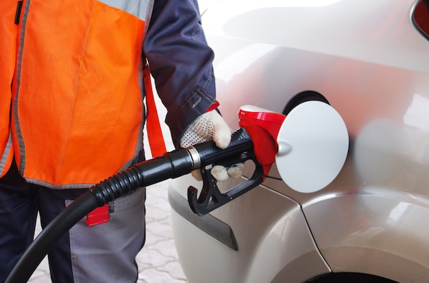 Bijtankende werknemer tankt de auto met benzine