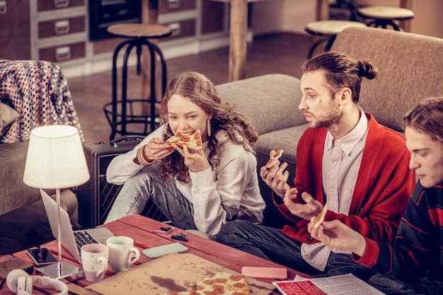 Bijtend stuk. mooie tienermeisje bijt stuk salami pizza lunchend met haar vrienden