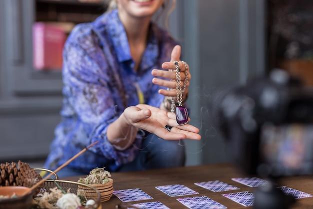 Bijzonder amulet. close-up van een mooie mooie ketting terwijl je in vrouwelijke handen bent
