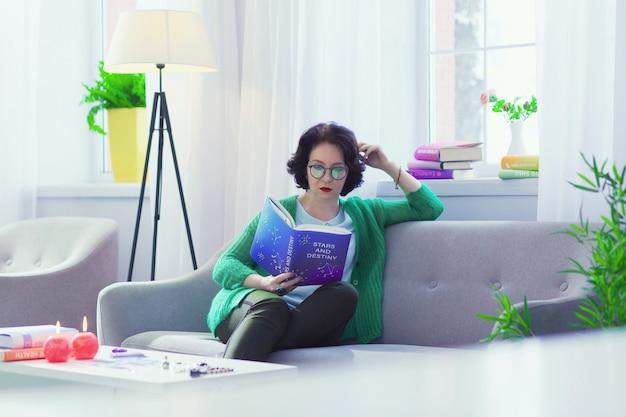 Bijzonder boek. aardige intelligente vrouw die betrokken is bij het lezen terwijl ze geïnteresseerd is in astrologie