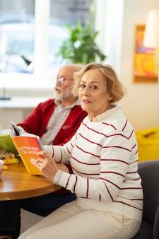 Bijzonder boek. knappe oudere vrouw die haar favoriete boek vasthoudt terwijl ze aan tafel zit