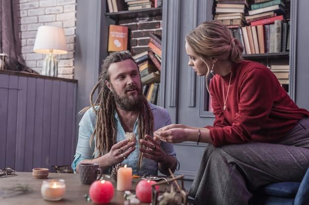 Bijzonder kristal. aardige man met een baard die met zijn bezoeker praat terwijl hij een speciaal kristal voor haar vasthoudt