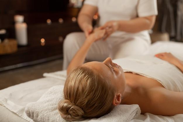 Bijzondere bewegingen. rustige dame met vastgebonden haar liggend met gesloten ogen op voorbereid bed terwijl masseuse ijverig de handen verwerkt