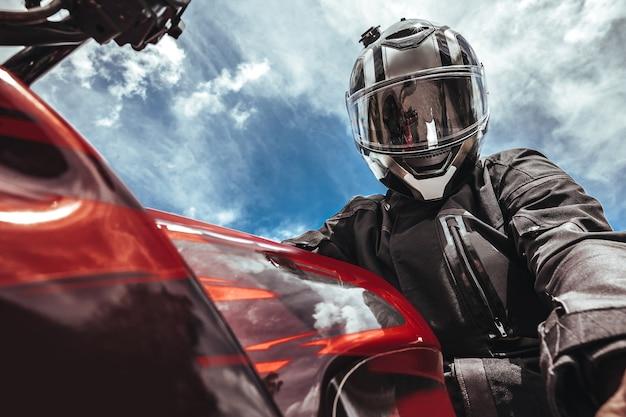 Biker in een helm zit op een motorfiets tegen de achtergrond van de lucht maakt een selfie