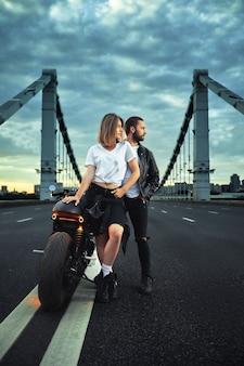 Biker man en meisje staat op de weg en kijkt in de verte. liefde en romantisch concept.
