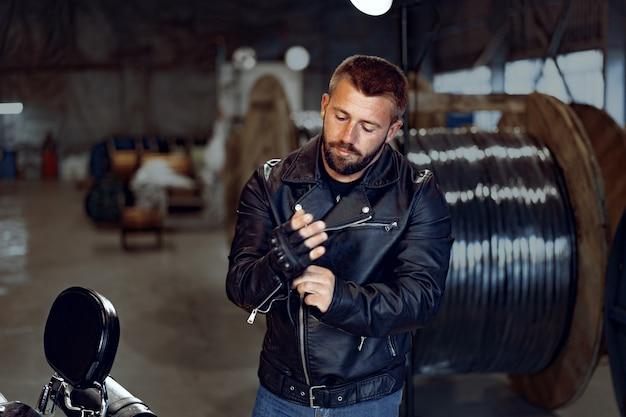 Biker man trekt zijn leren handschoenen aan om te rijden
