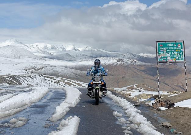 Biker op de top van de tanglang la-pas is de op een na hoogste berijdbare weg ter wereld