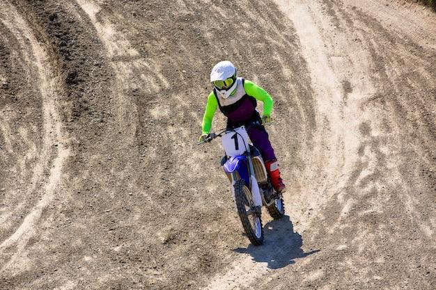 Biker op motorfiets stunts tijdens het rijden op het achterwiel zijaanzicht