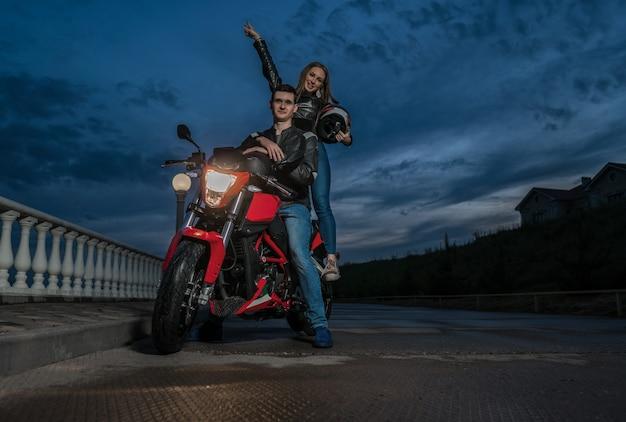 Biker paar man en vrouw op een zwarte en rode kleur sport motorfiets. nacht zicht