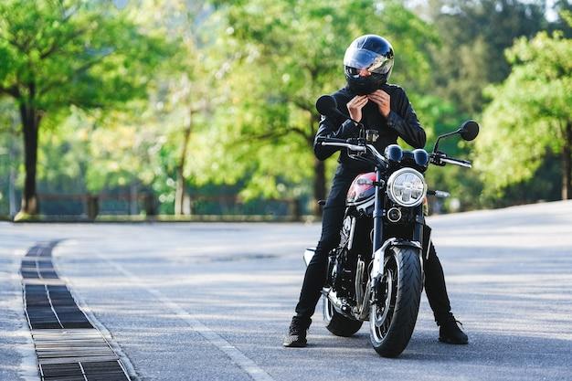 Biker zit op een motorfiets en maakt zijn helm vast ter voorbereiding op de rit