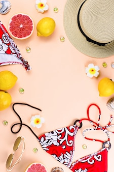 Bikini badpak met stro hoed, bloemen en fruit, platte ontwerp, zomer concept. strandbestemming, zomermode