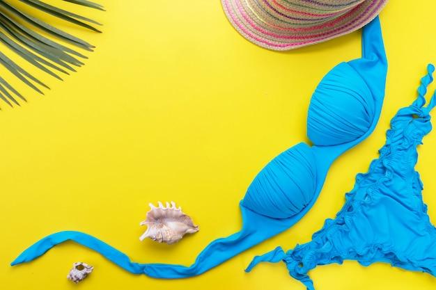 Bikini badpak met tropische print, zilveren glitter platte sandalen, strohoed, rieten strandtas, sarong, tropische palmbladeren op roze achtergrond. bovenaanzicht van badmode en strandaccessoires van de vrouw.