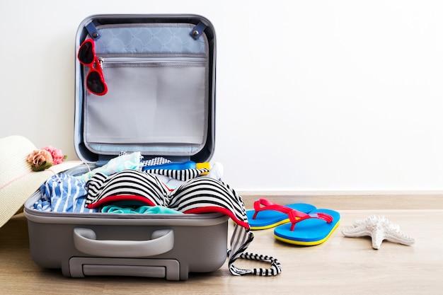 Bikini en kleding in bagage op de laminaatvloer