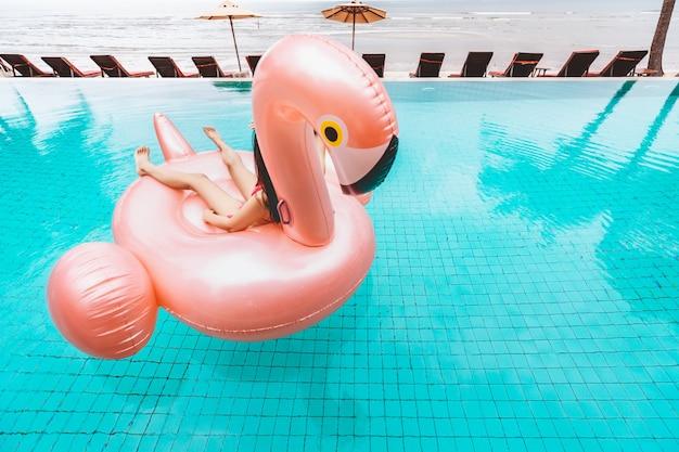 Bikini vrouw ontspanning op zwembad float