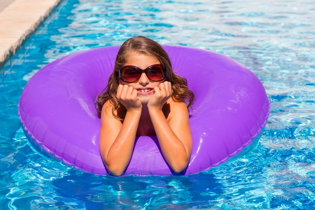 Bikinimeisje met zonnebril en opblaasbare poolring