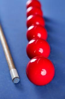 Biljart poolstick met rode ballen rij