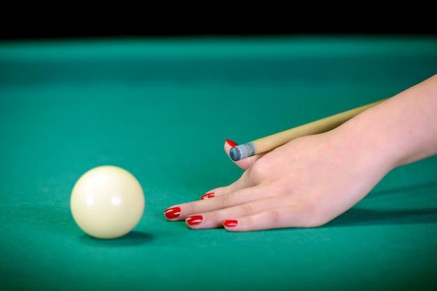 Biljartballen op groene tafel en witte bal op voorgrond.