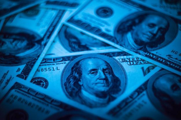 Biljetten van honderd amerikaanse dollars zijn verspreid over het oppervlak.