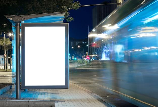 Billboard met licht in het stadscentrum 's nachts met bus in beweging