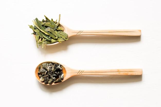 Biluochun en longjing. chinese blad groene thee in een lepel op een witte achtergrond.