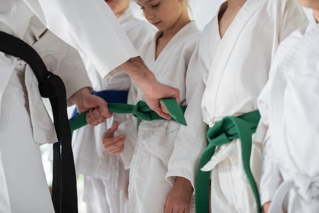 Bindende riem. ervaren aikido-trainer met zwarte band-bindband voor zijn leerling voor de wedstrijd