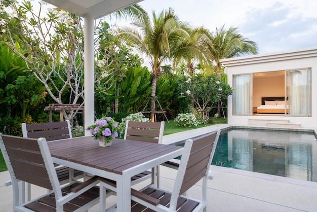 Binnen- en buitenontwerp van eettafel buiten bij het zwembadterras van villa, huis en huis