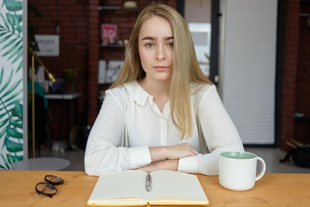Binnen foto van ernstige jonge vrouw in stijlvolle blouse handen rusten op houten tafel, cappuccino hebben tijdens koffiepauze en schrijven in beurt